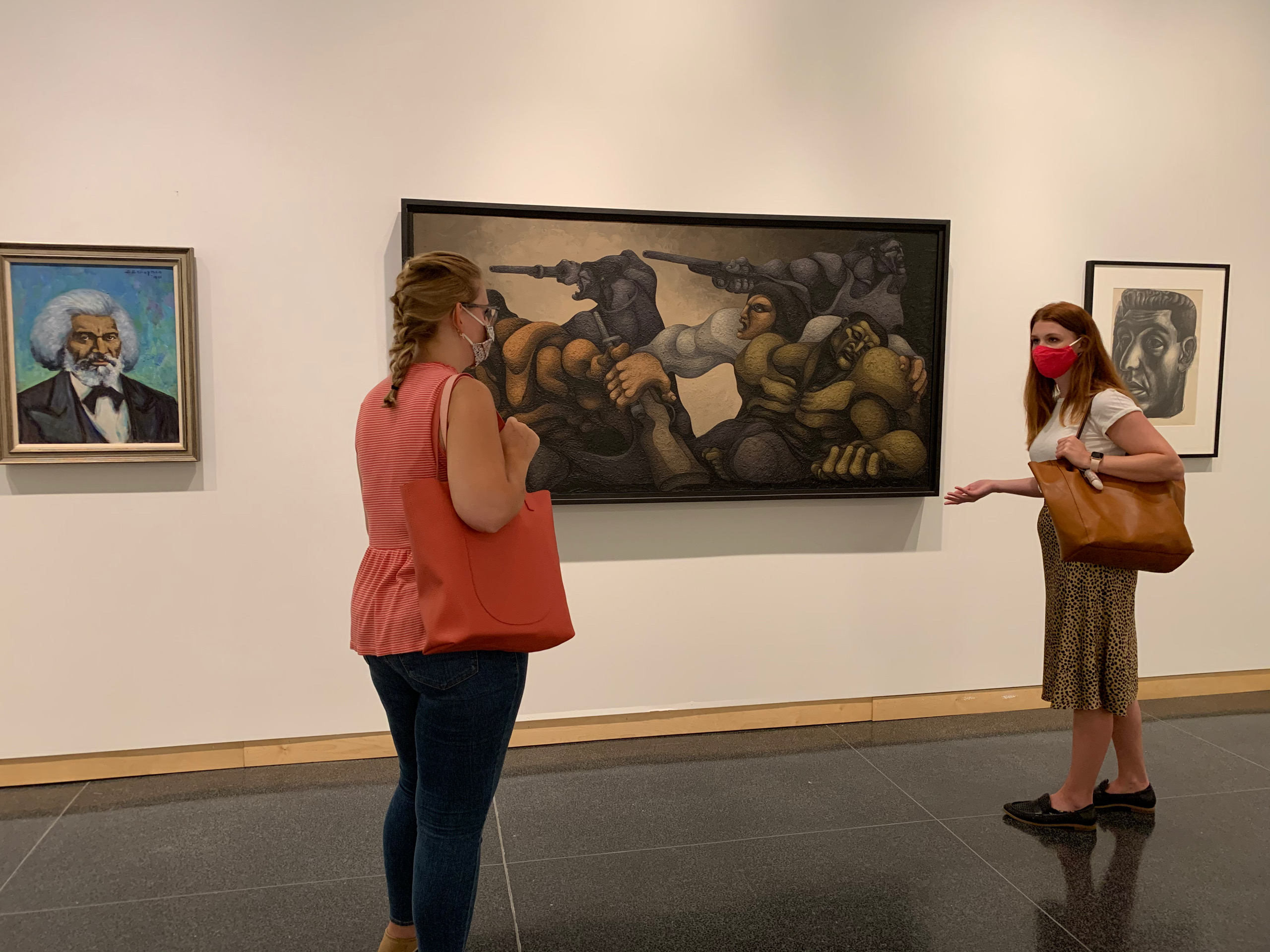 Two women in a museum, having a conversation in front of artwork