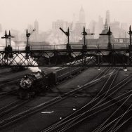 black and white phot of a train depot with a city skyline in background