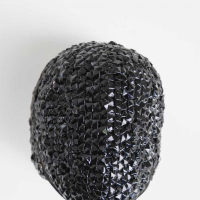 Black fencing mask with shiny black jewels adhered to the entire surface catching the light