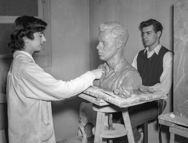 black and white photo of a woman on the left with a white coat on with dark hair, sculpting a bust with a model posing at far right