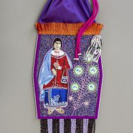 Purple drawstring pouch with tassels at bottom, fringe at the upper half, and beaded woman wiht a red shirt and blue skirt next to beaded floral