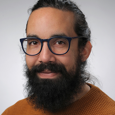 portrait of a male with dark hair pulled back and a beard. wearing black glasses and wearing a brown sweater