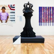 Exhibition gallery with wooden maple floorsand in the center, a large black sculture that resembles a column, on the left behind in a painting of a woman with blue and red horizontal stripes and on the left a painting wiht blue vertical stripes and read design underneath